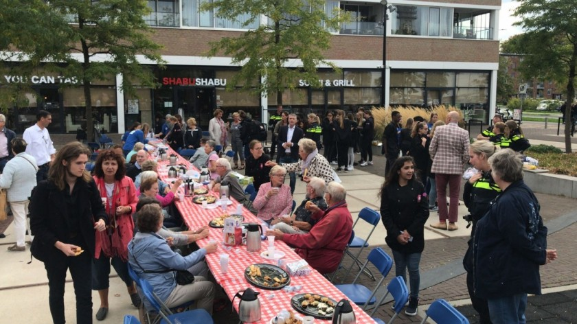 Scholieren en ouderen aan de high tea in de Baronie